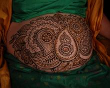 gorgeous paisley henna design graces this pregnant belly