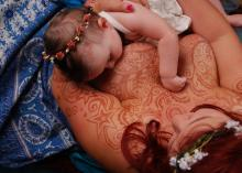 sun, moon and stars grace this mama's chest as breastfeeding body art