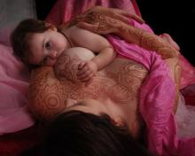 sweet baby girl breastfeeds, mama has picked out some gorgeous full chest henna tattoo